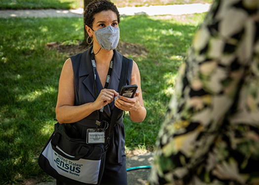 Female Census taker wearing a face mask and her badge talking to a resident