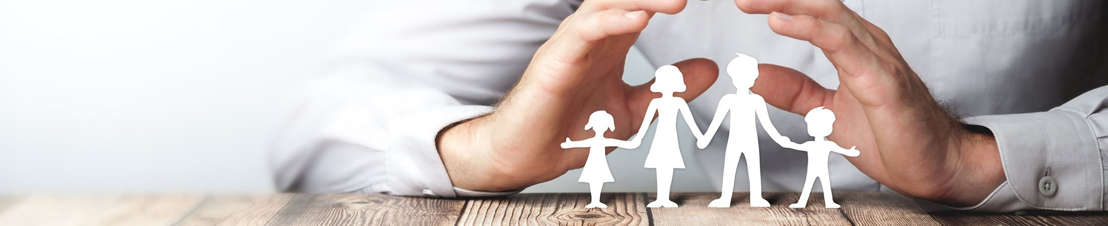 hands sheltering paper cut out of family