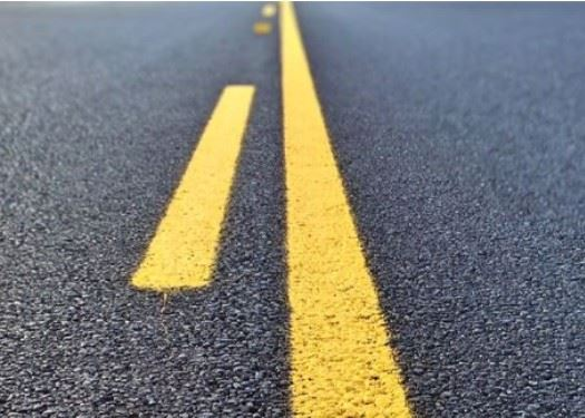 Close up photo of asphalt road with yellow stripes