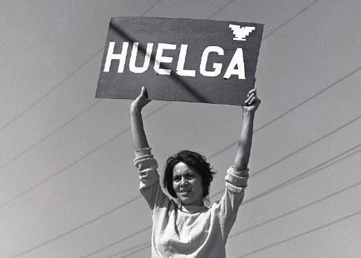 Lady holding up a Huelga Sign