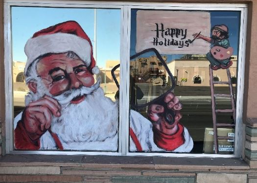 Santa on a window holding a mirror