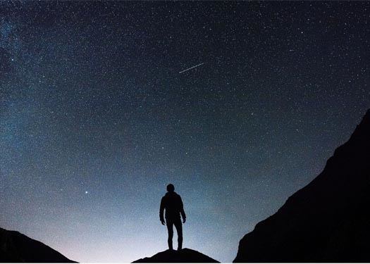 Human Person standing on mountaintop looking into space