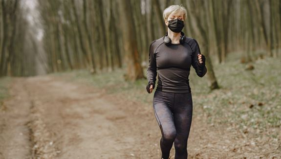 Woman With a Face mask running outside