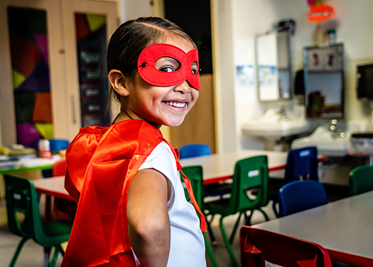 Little girl wearing a red superhero costume at a classroom