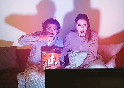 Scared couple watching a movie on their TV
